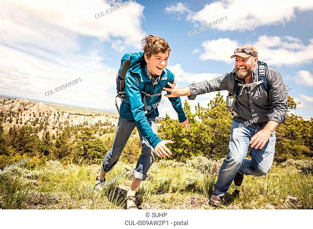 Father and teenage son chasing each other on hiking trip, Cody, Wyoming, USA
