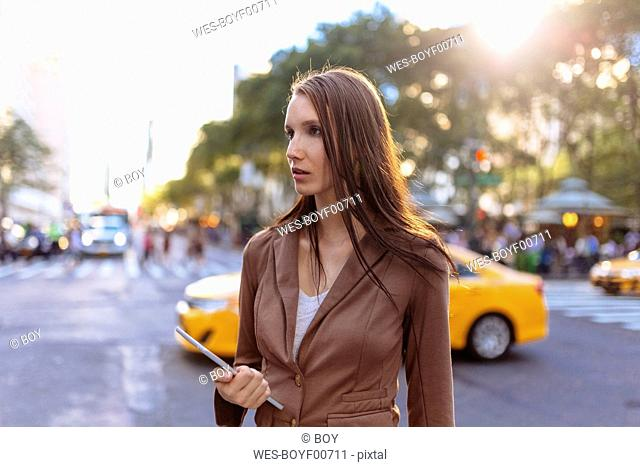 USA, New York, Manhattan, young businesswoman with tablet watching something