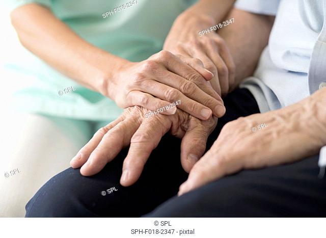 Care worker holding senior man's hands