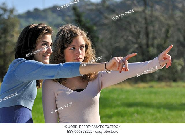 Two teenage girls pointing at field