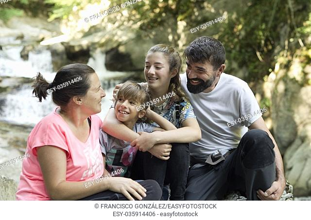 Family sitting on some rocks next to a river in the Irati Seva of Navarra, Spain