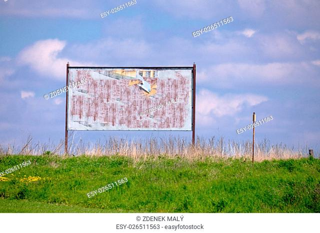 big empty billboard for advertising in spring countryside. Empty billboard with old torn posters with space for text