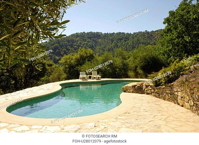 Curved swimmingpool with recliners on paving surrounded by low trees in Southern Spain