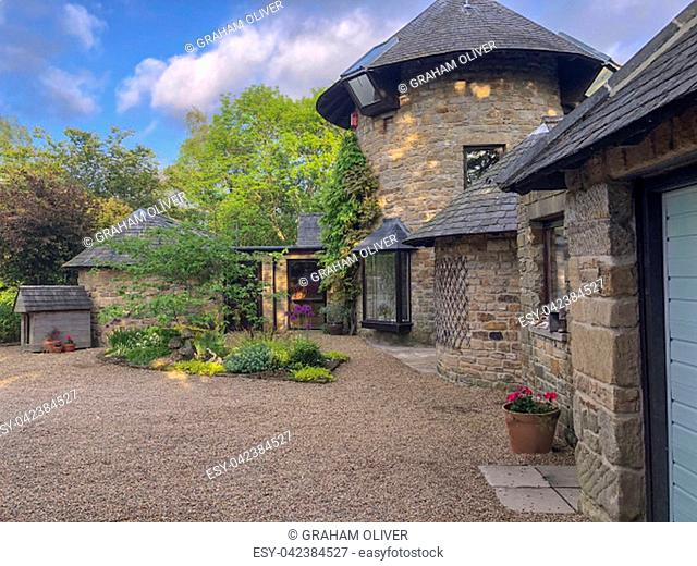 A wide view shot of a luxurious windmill converted home in the countryside alongside trees and a stone driveway