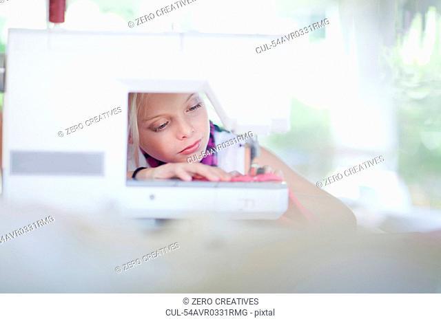 Girl using sewing machine