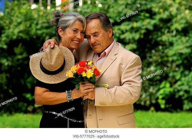 Ein aelteres elegantes Paar umarmt sich im Garten, Hamburg 2006 - Hamburg, Germany, 11/09/2006
