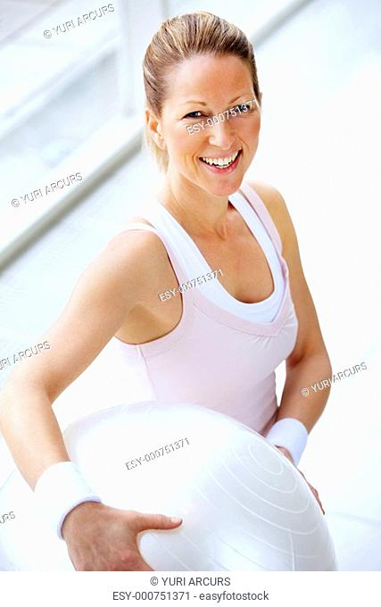 Smiling fit mature woman holding a fitness ball
