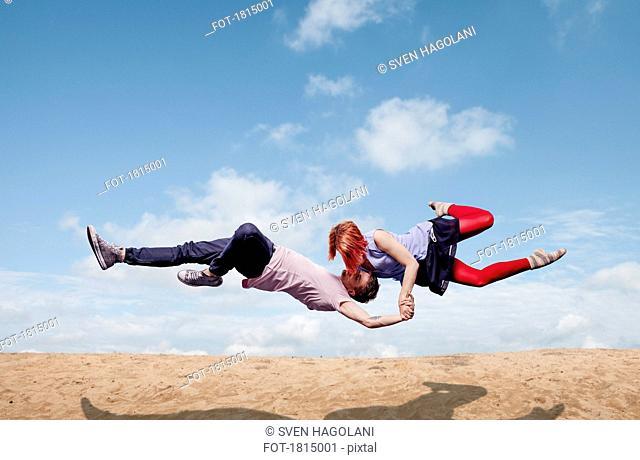 Modern aerialist dancers performing, flying over beach