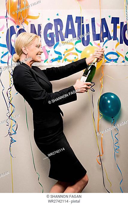 Businesswoman opening bottle of champagne
