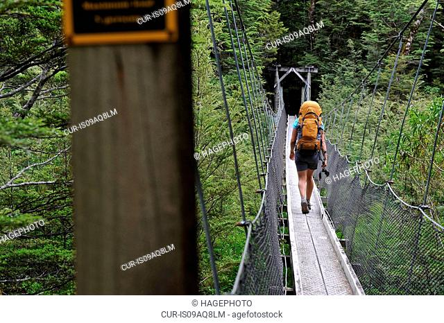 Woman crossing footbridge, New Zealand