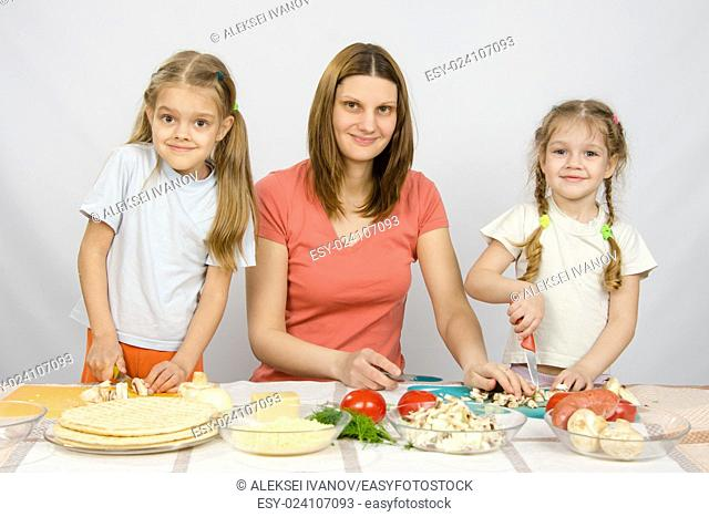 Woman with two young girls at the table prepared ingredients for pizza