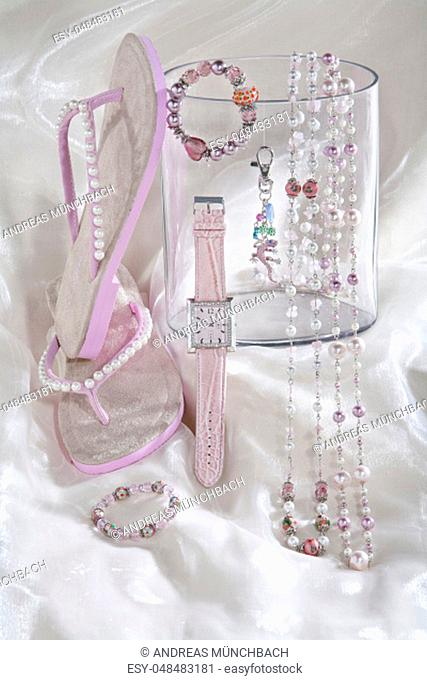 still life of pink necklace chains watch and flip flops on white satin background