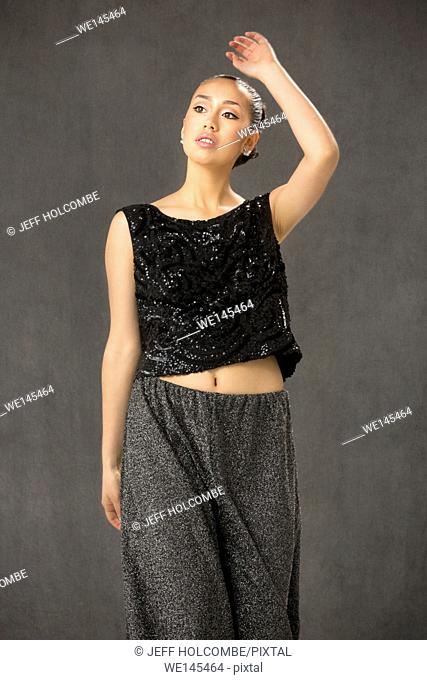 Attractive young woman dancing, nearly full length, in black top and baggy gray pants in studio shot on gray background