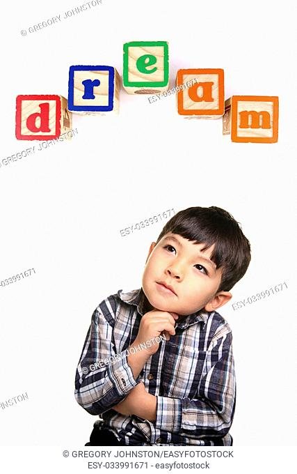 A young boy in a day dreaming pose under the word blocks