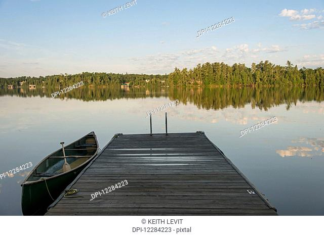 Canoe beside a wooden dock on a tranquil lake; Ontario, Canada
