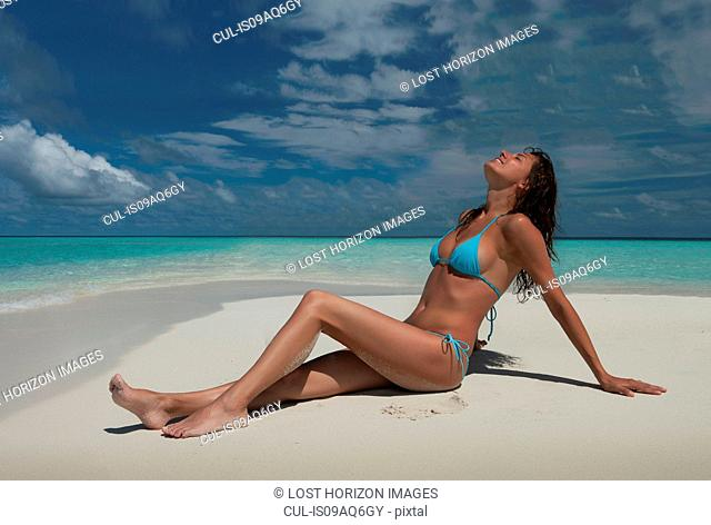 Mid adult woman sitting on beach, Ari Atoll, Maldives