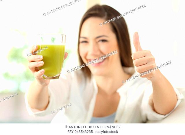 Proud woman showing a vegetable juice sitting on a couch in the living room at home