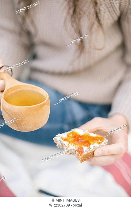 A woman holding a cup of tea and a slice of bread and jam