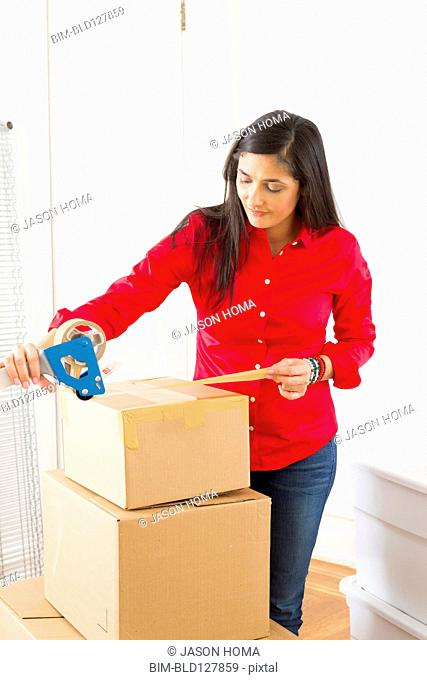 Mixed race woman packing cardboard boxes