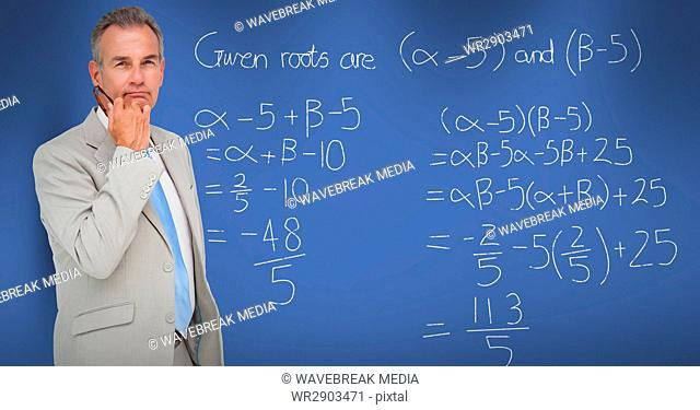 Thoughtful businessman standing by math equation