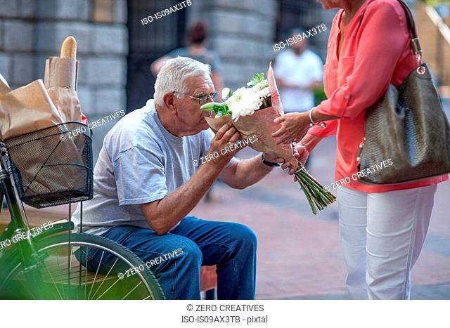 Senior man smelling bouquet on city steps
