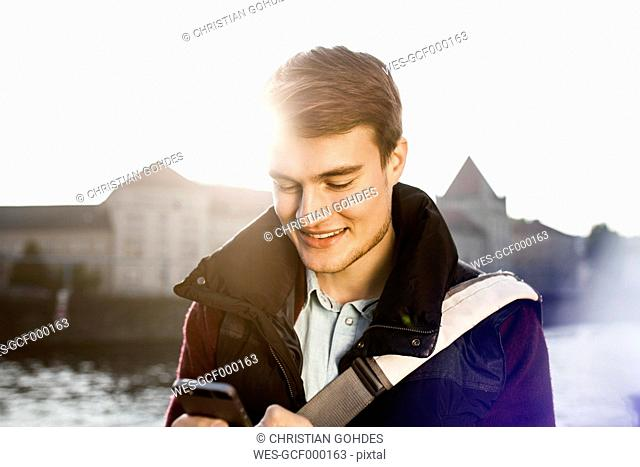 Germany, Berlin, young man holding smartphone at River Spree