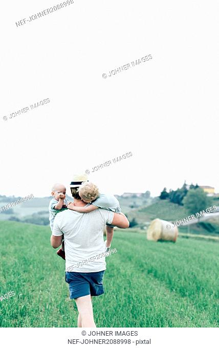 Father carrying children through field