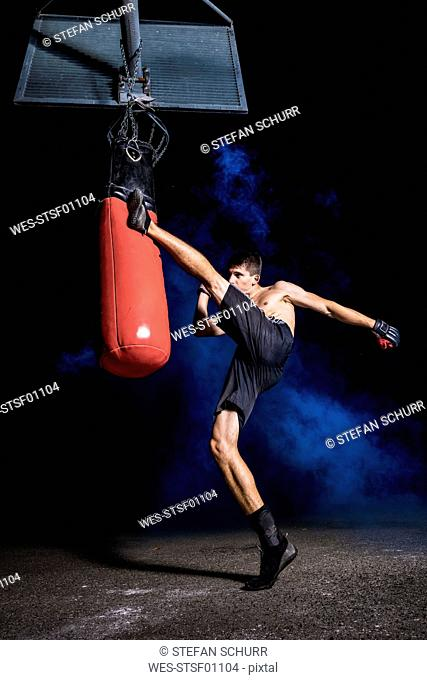Kickboxer exercising with punch bag