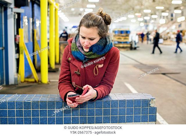 New York City, USA. Young, brunette woman using her smartphone to read e-mail messages while leaning on a wall inside the New Fulton Fish Market, Hunts Point