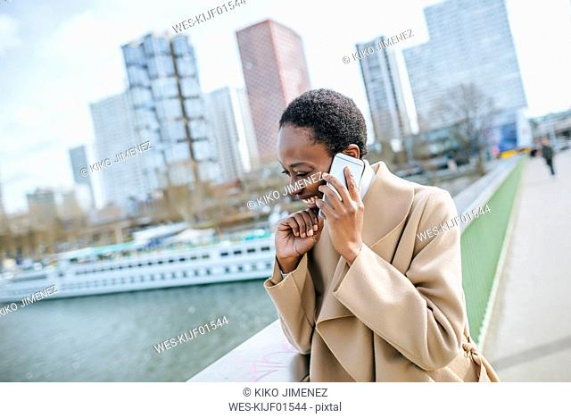 France, Paris, Young businesswoman talking on the phone