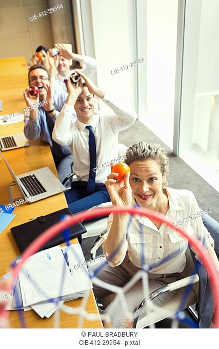 Business people aiming plastic balls at basketball hoop in conference room