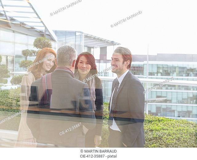 Business people talking on office balcony