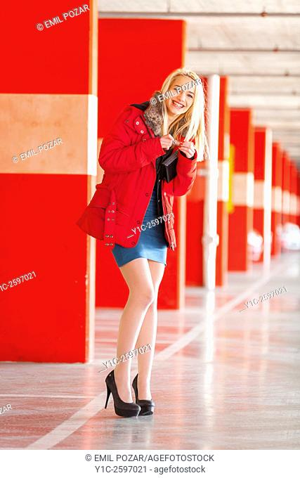 Young lady is happy in empty Red-walled parking-lot