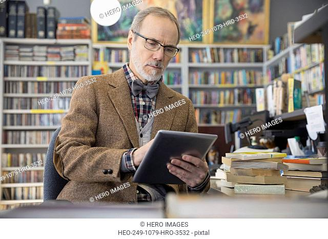 Bookstore owner using digital tablet