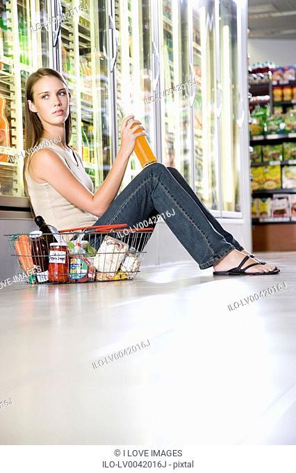 Woman sitting on a supermarket floor drinking
