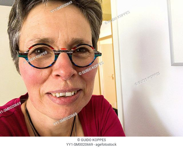 Tilburg, Netherlands. Portrait of a mature adult woman wearing glasses, while sitting in a photographers studio