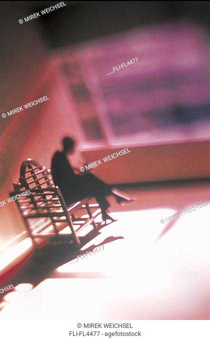 Overview, Silhouetted Businesswoman Sitting on Bench in Empty Room