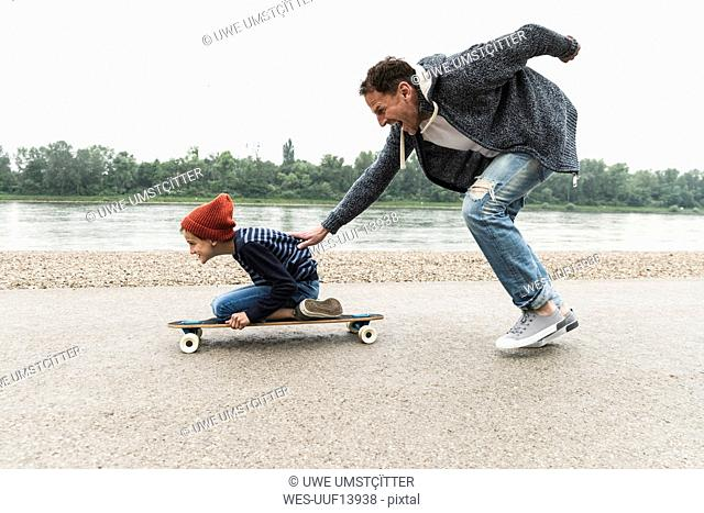 Happy father pushing son on skateboard at the riverside