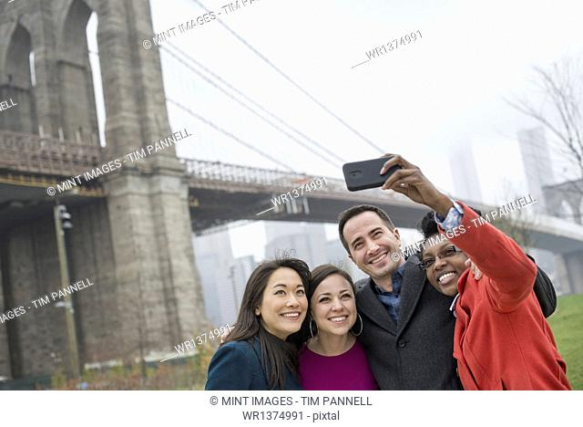 New York city. The Brooklyn Bridge crossing over the East River. Four friends taking a picture with a phone, a selfy of themselves