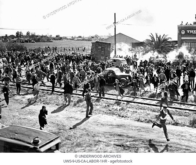 Stockton, California: April 23, 1937.Striking cannery workers at odds with a truckload of spinach being taken into the newly reopened cannery
