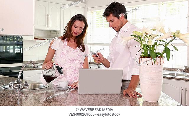 Pretty woman making her husband a coffee in the morning