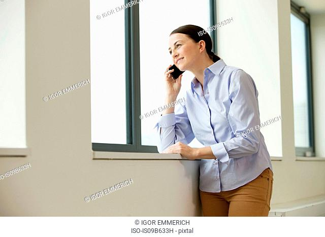 Woman standing beside window in empty office space, using smartphone