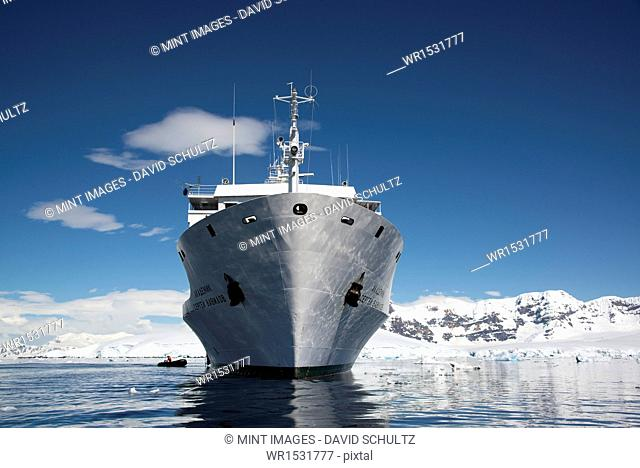 An Antarctic cruise ship with inflatable zodiacs on the calm waters among ice floes and mountainous landscape