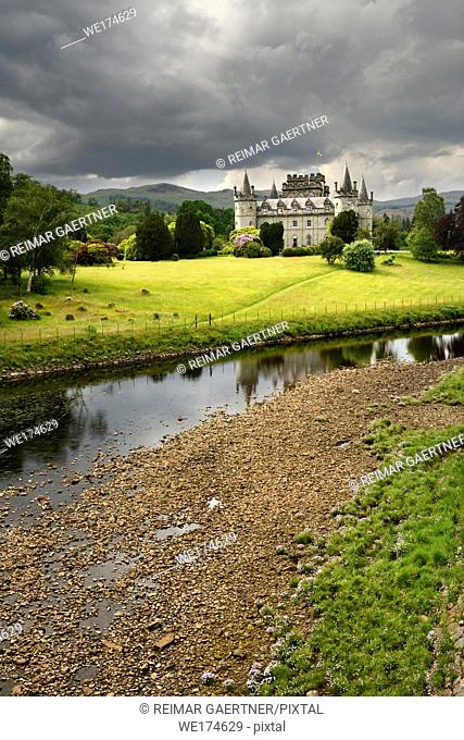 Inveraray Castle in sun reflected in the River Aray at Loch Fyne with dark clouds and sunshine in the Scottish Highlands Scotland UK