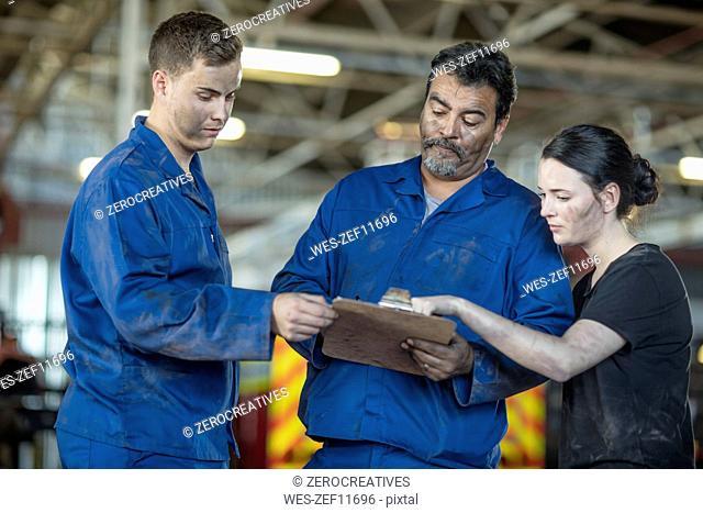 Mechanics working at fire brigade workshop reading check list