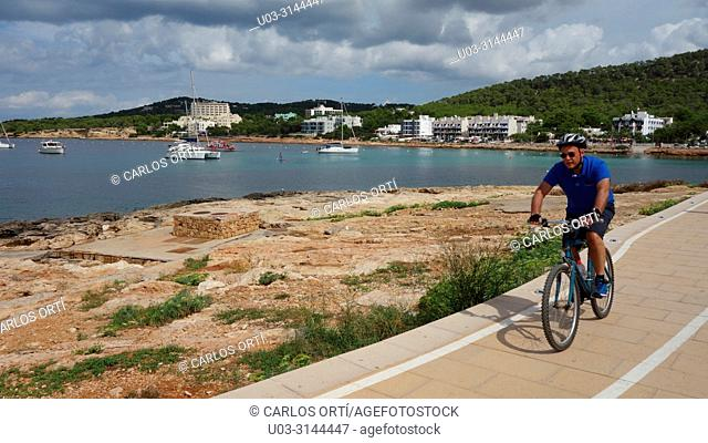 tourist riding a bicycle in the mediterranean town of Sant Antoni de Portmany, the second town of the balearic island of Ibiza, Spain, Europe