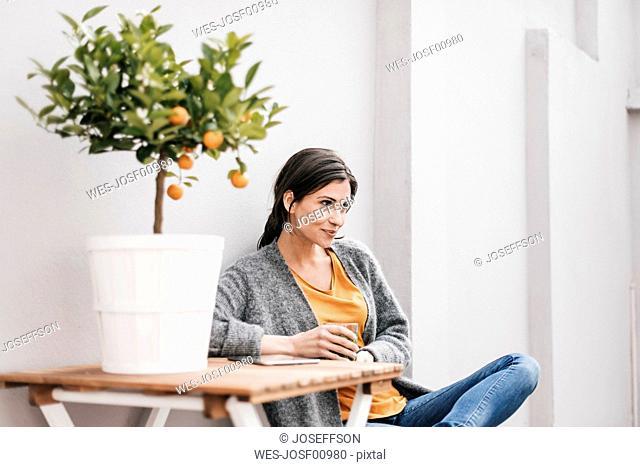 Woman relaxing next to orange tree
