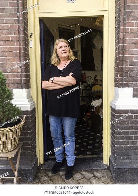 Tilburg, Netherlands. Mature adult female vintage shop owner standing firm in the doorway of her retro store, waiting for new customers