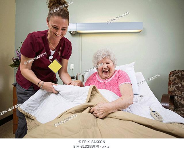 Caucasian nurse with laughing patient in hospital bed