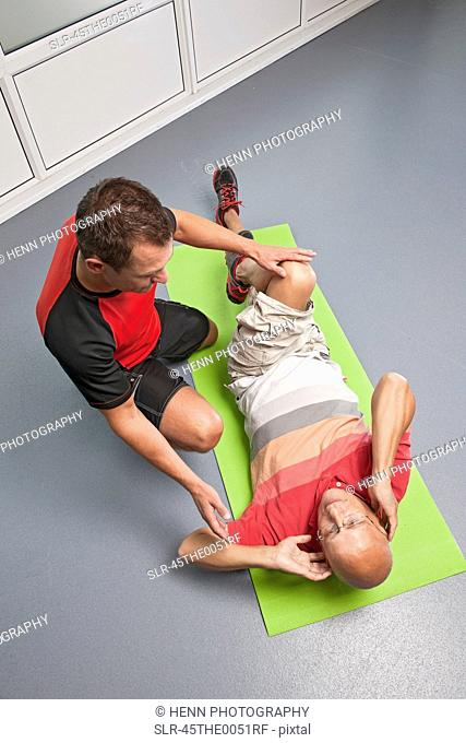 Trainer working with client in gym